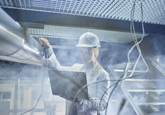 Técnico femenino que trabaja en tuberías, usando laptop - foto de stock