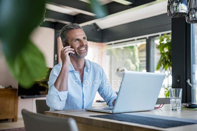 Улыбающийся взрослый мужчина дома с помощью мобильного телефона и ноутбука за столом — стоковое фото