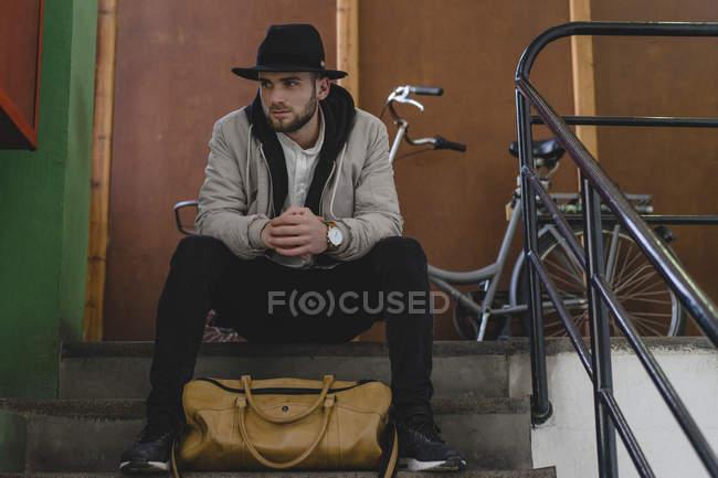 Bearded man wearing black hat, sitting on steps, travel bag — Stock Photo