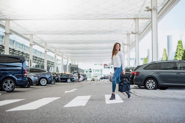 Giovane donna con borsa crossing street a zebra crossing — Foto stock