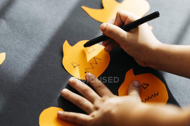 Petit garçon qui peint des visages sur des citrouilles en carton pour l'Halloween — Photo de stock