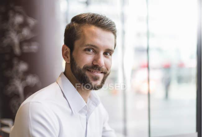 Retrato de um jovem empresário sorridente à janela — Fotografia de Stock