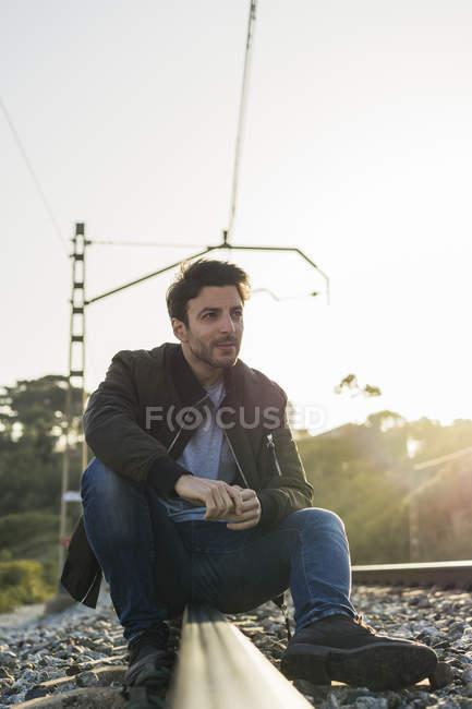 Jeune homme assis sur la voie ferrée — Photo de stock