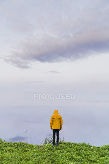 Lonely man in yellow rain coat standing on green grass at lake, looking at fog — Stock Photo