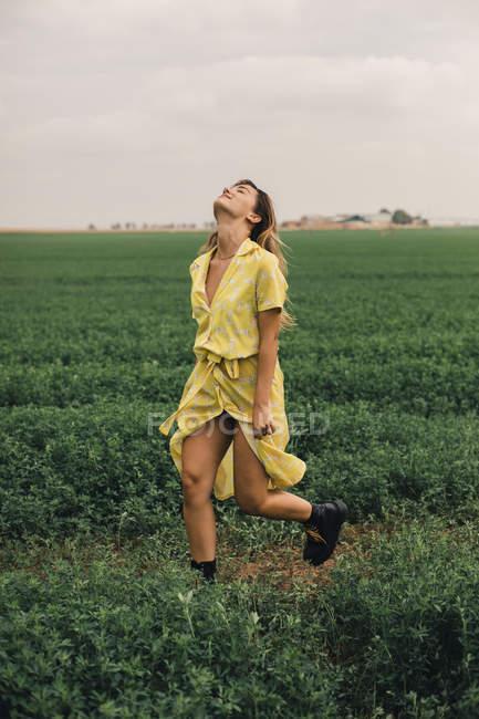 Молода жінка в жовтій сукні, що йде на зеленому полі. — стокове фото