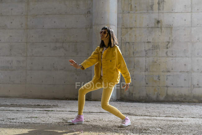 Woman wearing yellow jeans clothes, dancing — Stock Photo