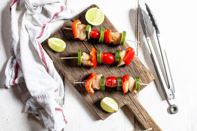 Spiedini di griglia con pollo crudo, pomodoro, peperone e zucchine su tagliere — Foto stock