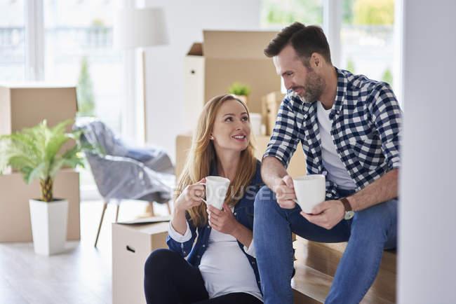 Uomo e donna incinta si trasferiscono in un nuovo appartamento con una pausa caffè — Foto stock