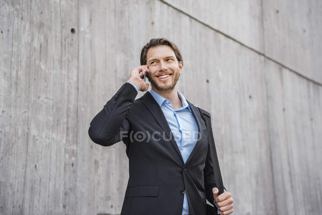 Homme d'affaires souriant au mur de béton parlant sur smartphone — Photo de stock