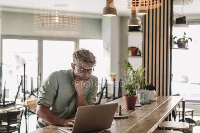 Молодий чоловік, який працює у стартовому кафе, використовуючи ноутбук — стокове фото