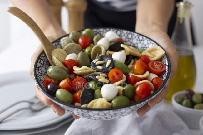 Woman showing mediterranean orecchiette with tomatoes, olives and mozzarella — Stockfoto