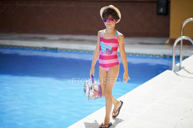 Giovane ragazza che cammina in piscina in estate con vestiti da bagno — Foto stock