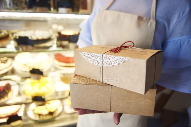 Крупный план женщины, держащей коробки с тортами в кондитерской — стоковое фото