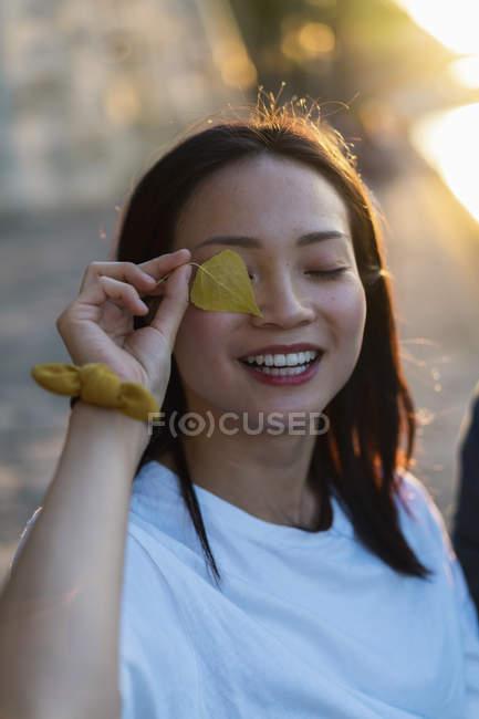 Портрет счастливой молодой женщины, держащей лист перед глазами — стоковое фото