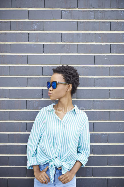 Woman with sunglasses standing in front of grey facade waiting — Stock Photo