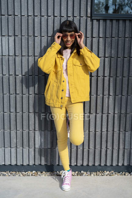 Young woman wearing yellow jeans clothes — Stock Photo