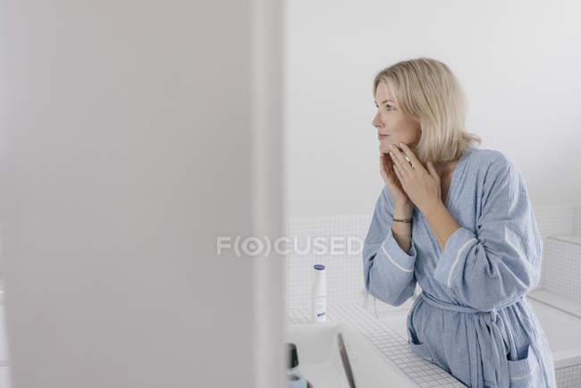 Літня жінка дивиться на дзеркало ванної — стокове фото