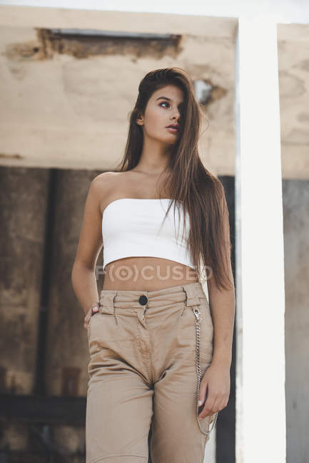 Brunette, long hair fashionable woman wearing white top and beige pants and posing in old building — Stock Photo