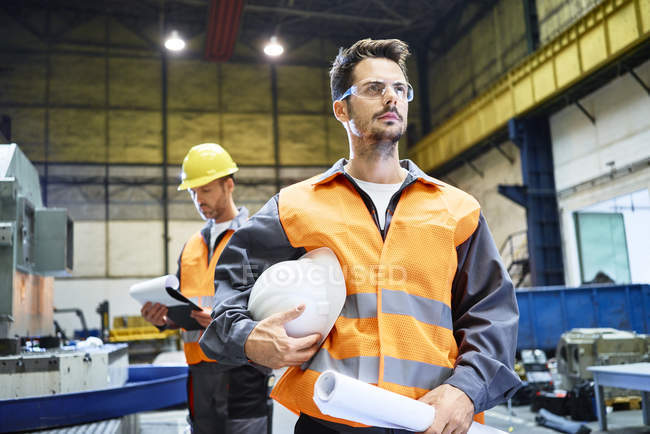 Men wearing protective workwear looking around in factory — Stock Photo