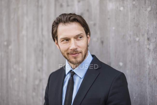 Porträt eines selbstbewussten Geschäftsmannes an Betonwand — Stockfoto