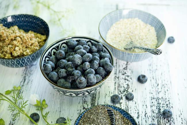 Cuencos de arándanos, semillas de chía negra, granola y amaranto - foto de stock