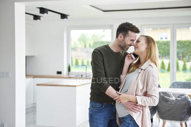 Hombre besando a mujer embarazada en piso vacío - foto de stock