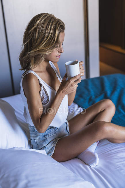 Jovem loira sentada na cama e bebendo café — Fotografia de Stock