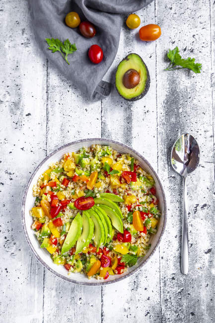 Bowl of bulgur salad with bell pepper, tomatoes, avocado, spring onion and parsley — Stock Photo
