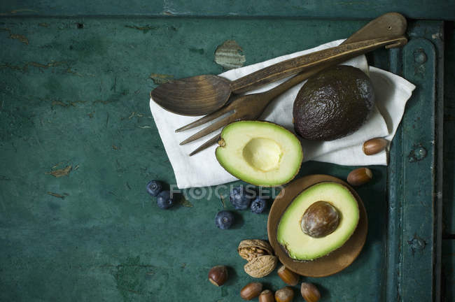 Cloth, salad cutlery, avocados, blueberries and nuts on green ground — Stock Photo