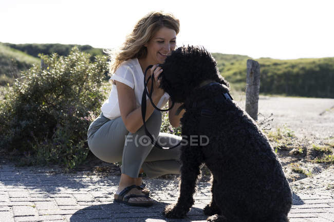 Woman petting cute dog in sunny countryside — Stock Photo