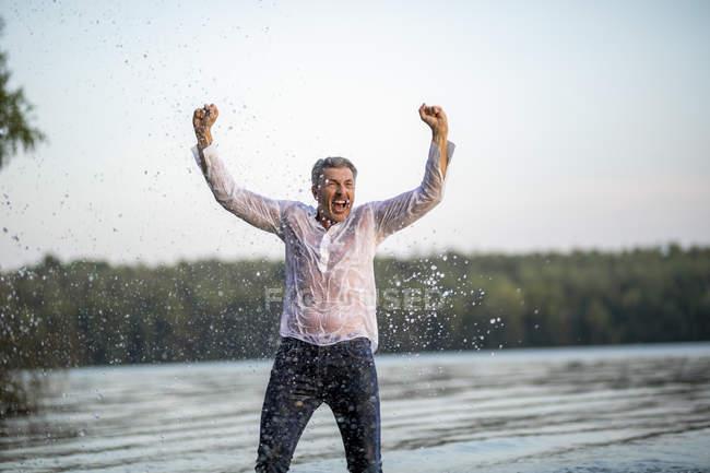 Gritando molhado maduro homem de pé no lago — Fotografia de Stock