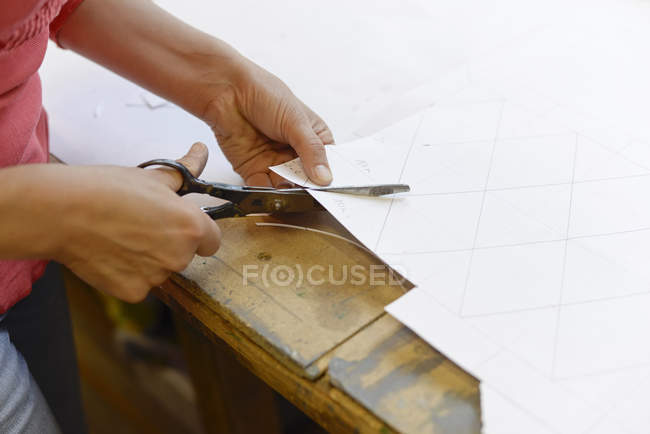 Close-up of woman cutting paper from draft in glazier's workshop — Stock Photo