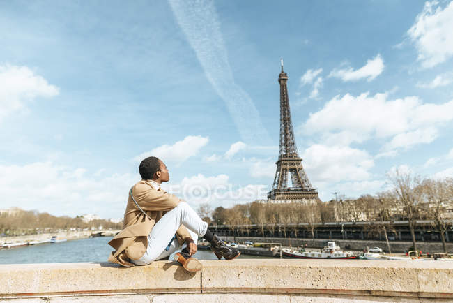 Франция, Париж, Женщина, сидящая на мосту через реку Сена и смотрящая на Эйфелеву башню — стоковое фото