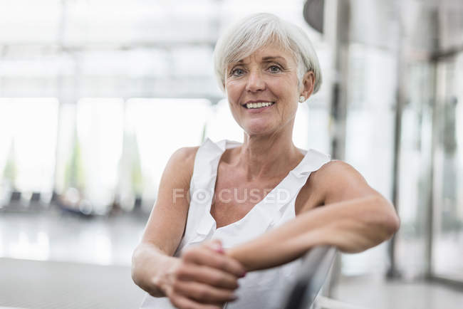 Portrait of smiling senior woman sitting in waiting area — Stock Photo