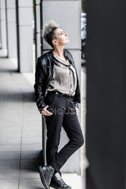 Punk woman leaning against column and looking up — Stock Photo