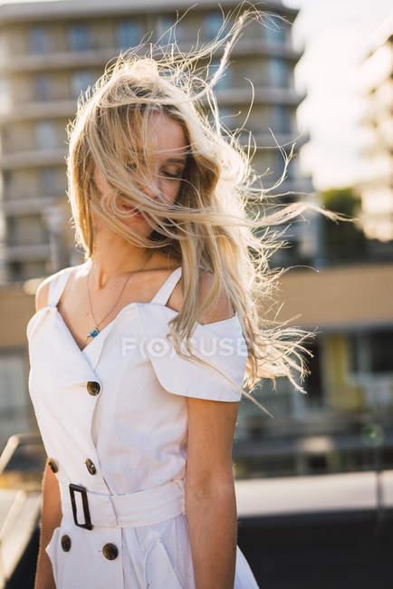 Jovem loira com olhos fechados, vestindo vestido branco ao ar livre — Fotografia de Stock