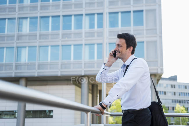 Smiling businessman on cell phone in the city — Stock Photo