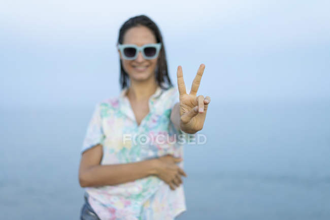 Smiling woman showing victory sign, close-up — Stock Photo