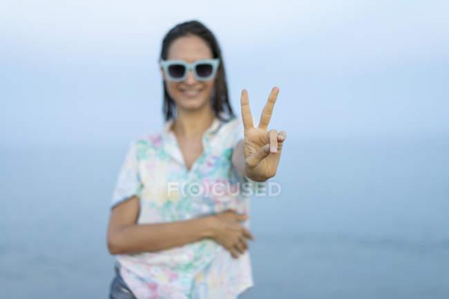 Sorrindo mulher mostrando sinal de vitória, close-up — Fotografia de Stock