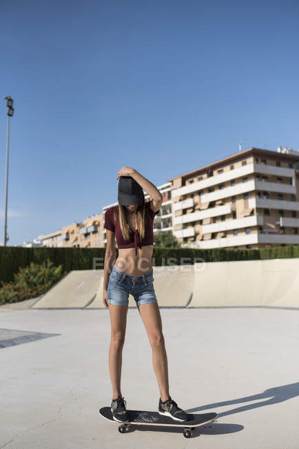 Young woman skateboarding in skate park — Stock Photo