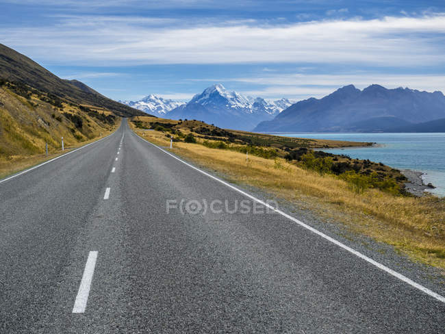 New Zealand, South Island, empty road with Aoraki Mount Cook and Lake Pukaki in the background — Stock Photo