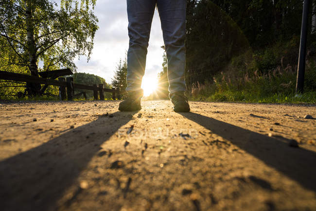 Man standing in street at sunset, low section — Stock Photo