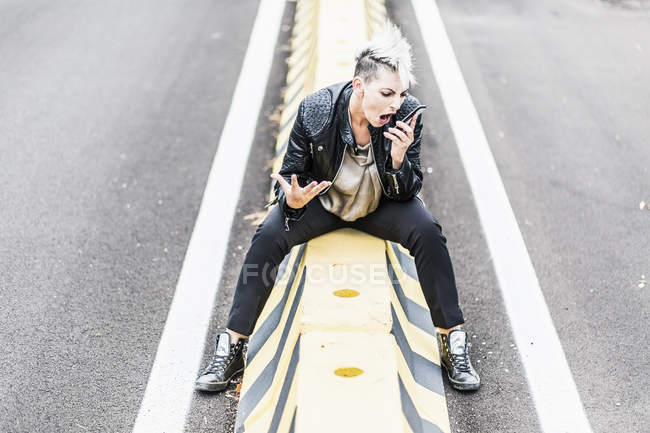 Aggressive punk woman sitting at roadside screaming into cell phone — Foto stock