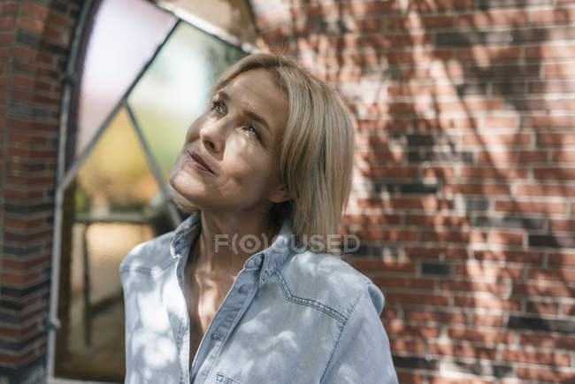 Portrait of mature woman in front of brick wall looking up — Stock Photo