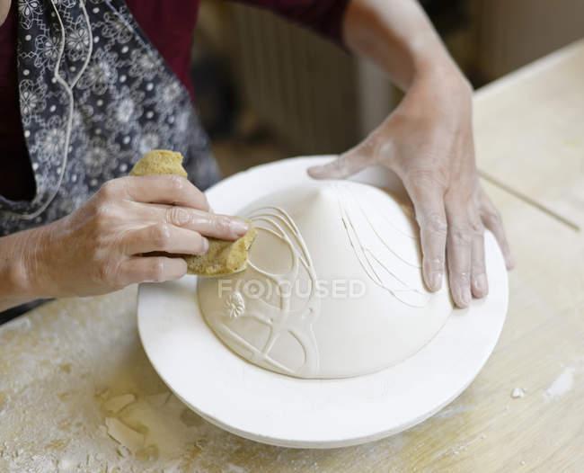Крупный план женщины, работающей в фарфоровой мастерской — стоковое фото
