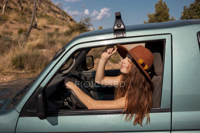 Smiling young woman wearing a hat sitting in a car in nature — Stock Photo