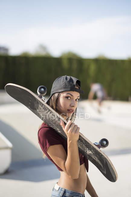 Jeune femme dans le stationnement de patin, portant la planche à roulettes — Photo de stock