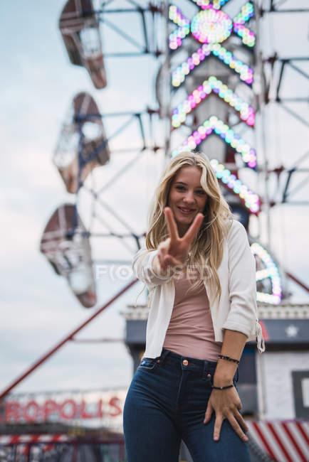 Sorrindo loira jovem olhando para a câmera e gesticulando paz com os dedos — Fotografia de Stock