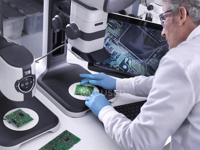 Ingénieur utilisant un stéréomicroscope 3D pour le contrôle de la qualité dans la fabrication de cartes de circuits imprimés pour l'industrie électronique — Photo de stock