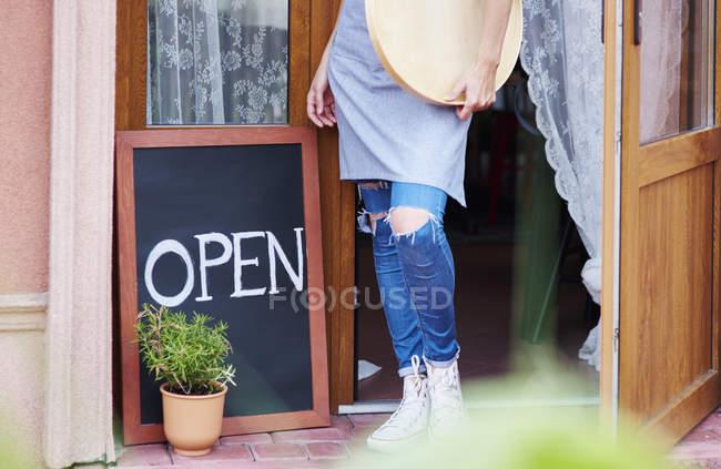 Жінка, що стоїть біля відкритих дверей acafe — стокове фото